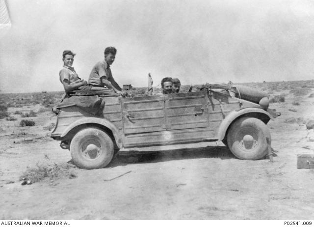Four unidentified members of No 3 Squadron RAAF, pose in a captured German Volkswagen Kfz 1 light car or Kubelwagen. (Small).jpg