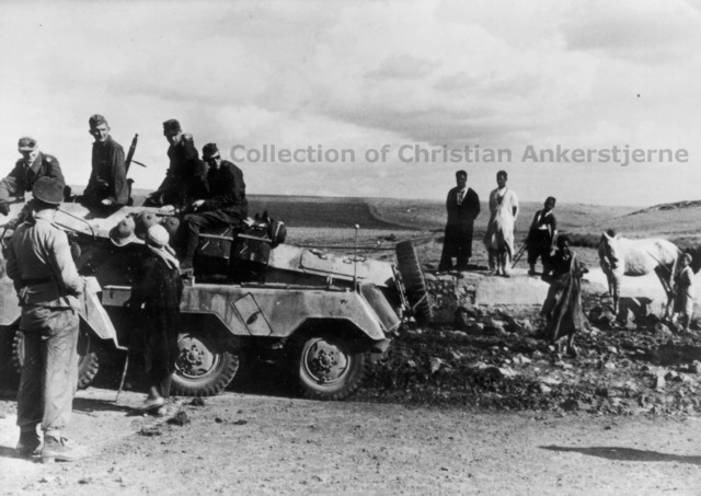 Sd. Kfz. 233 in Tunesia at a small water stop. Note the western clothes on the civilians.jpg