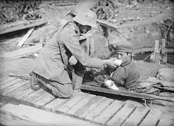 20.9.a German prisoner attending to a wounded comrade.jpg