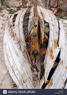 the-wrecked-wooden-hull-of-a-boat-on-the-beach-C47E2R.jpg
