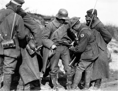 A1 Australian_soldiers_searching_German_POWs_for_souvenirs_in_October_1918.jpg
