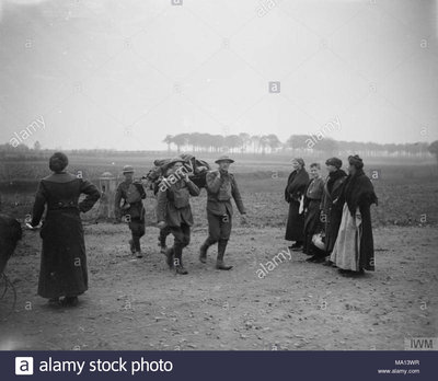 A2 the-hundred-days-offensive-august-november-1918-battle-of-courtrai-belgian-refugee-women-matching-british-wounded-of-the-monmouthshire-regiment-being-brought-in-near-heule-15-october-1918-MA13WR.jpg