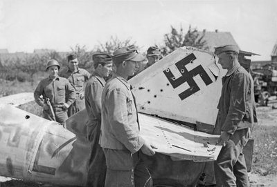 German-prisoners-of-war-wearing-German-uniform-caps-dismantled-a-Messerschmitt-Me-262-jet-fighter-for-scrap-in-a-small-town-southeast-of-Wurzburg-Germany-in-the-summer-of-1945.-AAF-768x520.jpg