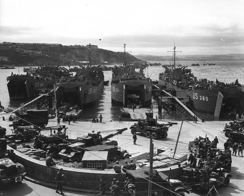 In preparation for the invasion, artillery equipment is loaded aboard LCTS at an English port. Brixham, England. 1 June 1944.jpg