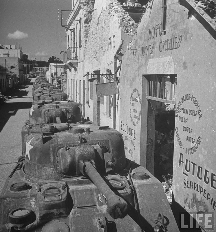 Sherman tanks lined up in the streets of the city by the US Armed Service Forces to be transported to the front.jpg