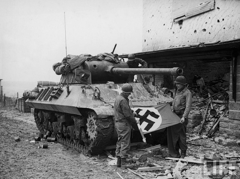 American soldiers of Patton's Third Army standing in front of their Sherman tank while rolling up a Nazi flag they have taken as a trophy after the capture of Bitberg.jpg
