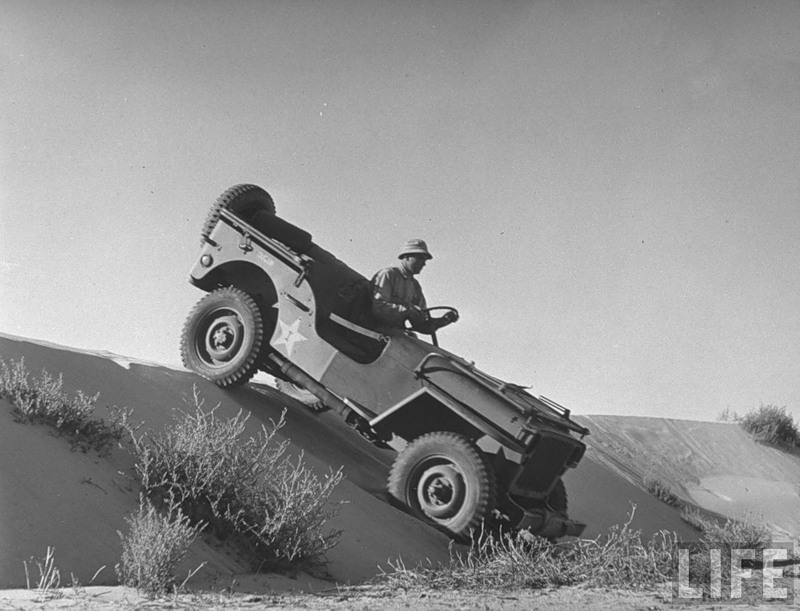 US Army jeep rolling down a sand dune during training maneuvers in the desert.jpg