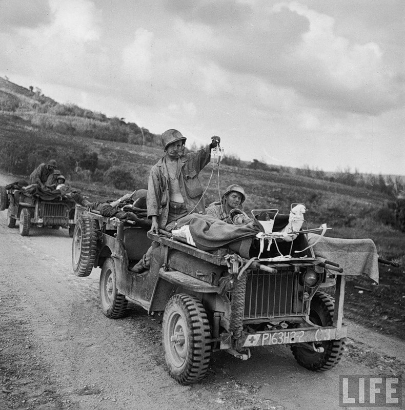 Wounded American soldier getting a plasma transfusion as he and his fellow wounded are transported from the front lines by Jeep for further treatment during the fight to take Saipan.jpg