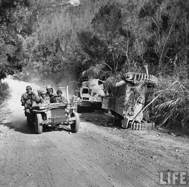 American soldiers guiding their Jeep around hulks of two Japanese light tanks destroyed during the fight for control of Saipan.jpg