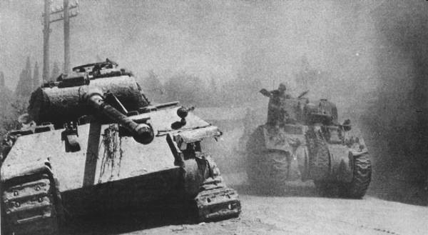 US Army Sherman Tank passing by a german Panzer V Panther disabled, probably in the Battle of Bulge.jpg