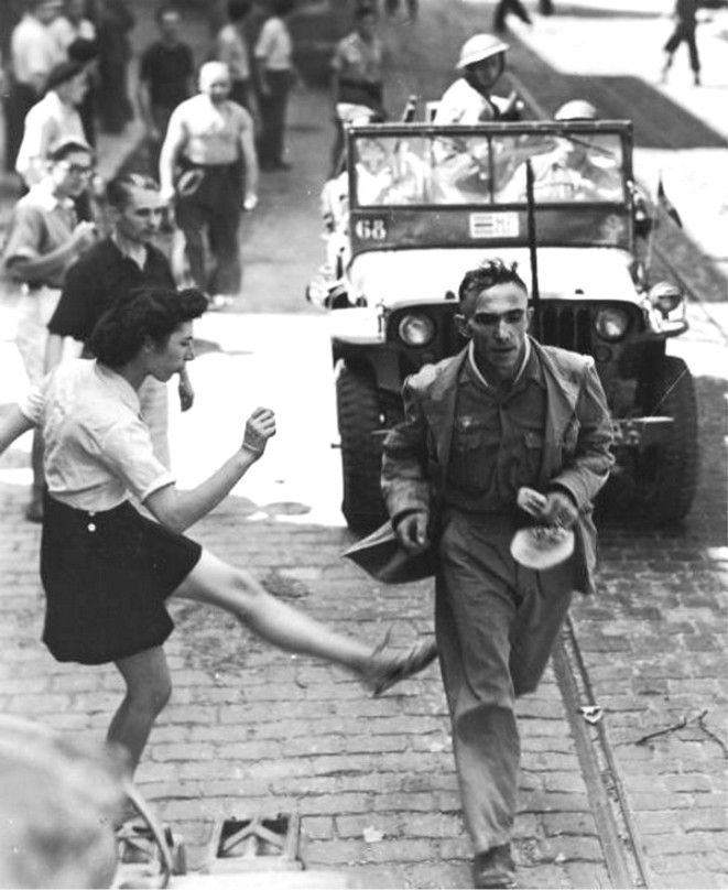 French woman in Toulon kicking a man who is being taken prisoner, probably a german or a german sympathizer, september 26, 1944.jpg