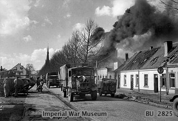 Supply lorries pass burning buildings in Bocholt, 31 March 1945. In the lead is an Austin K5, with a CMP Chevrolet following behind..jpg