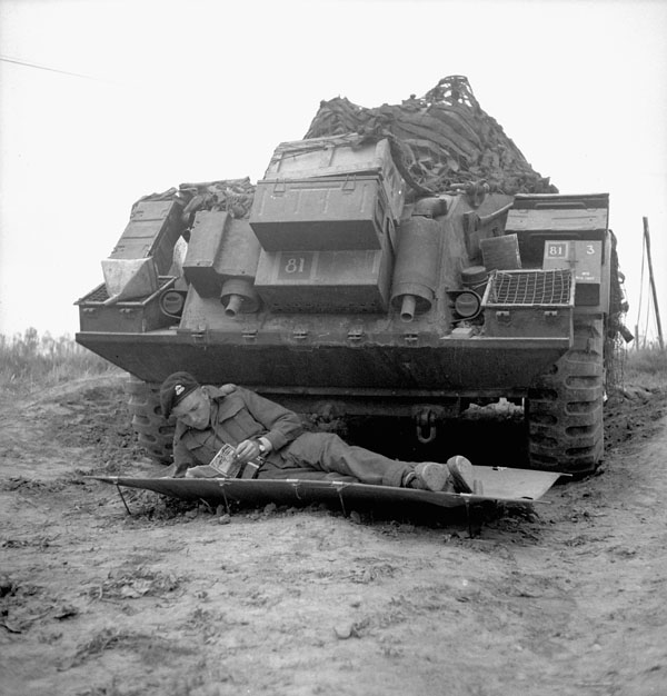 Trooper Ernie Tester of the 12th Manitoba Dragoons lying on a cot in front of a Sherman tank of a Canadian armoured regiment..jpg