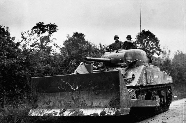 American-soldiers-drive-a-Sherman-tank-equipped-with-a-bulldozer-shovel.-France-August-7-1944.jpg