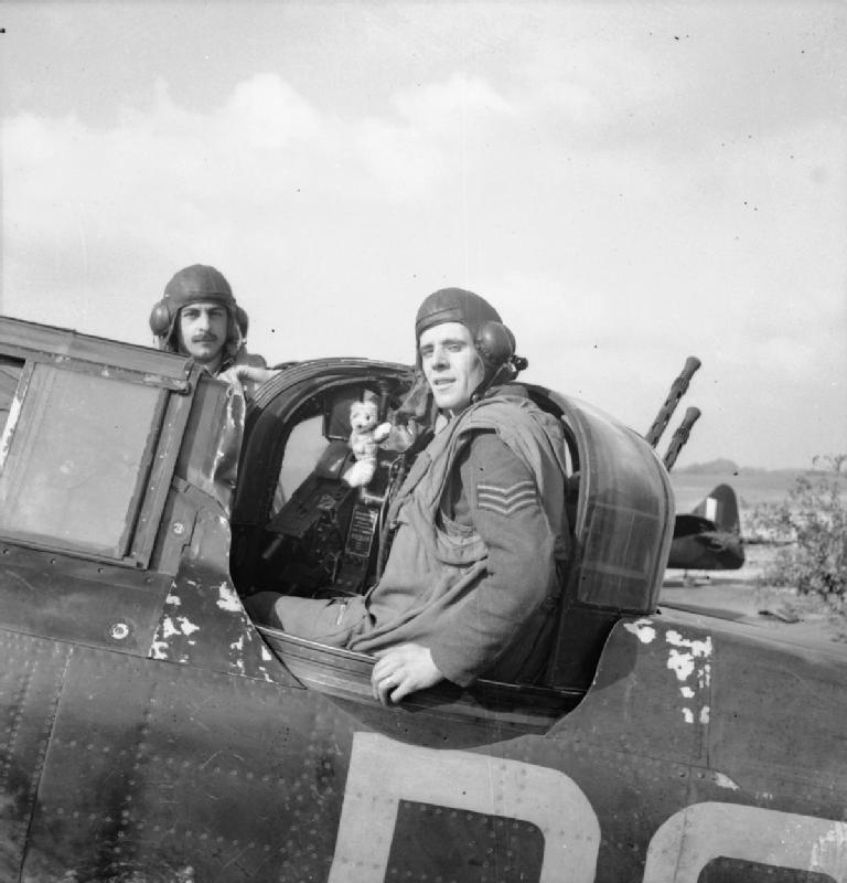 Flight Sergeant E R Thorn (pilot, left) and Sergeant F J Barker (air gunner) of No 264 Squadron RAF and their Teddy Bear mascot,.jpg